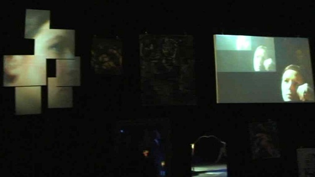 Live footage of the performer projected on the screens set among the paintings