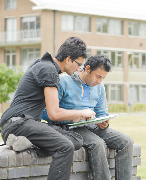 A pair of students studying on a bench in front of HumSS building at the University of Reading