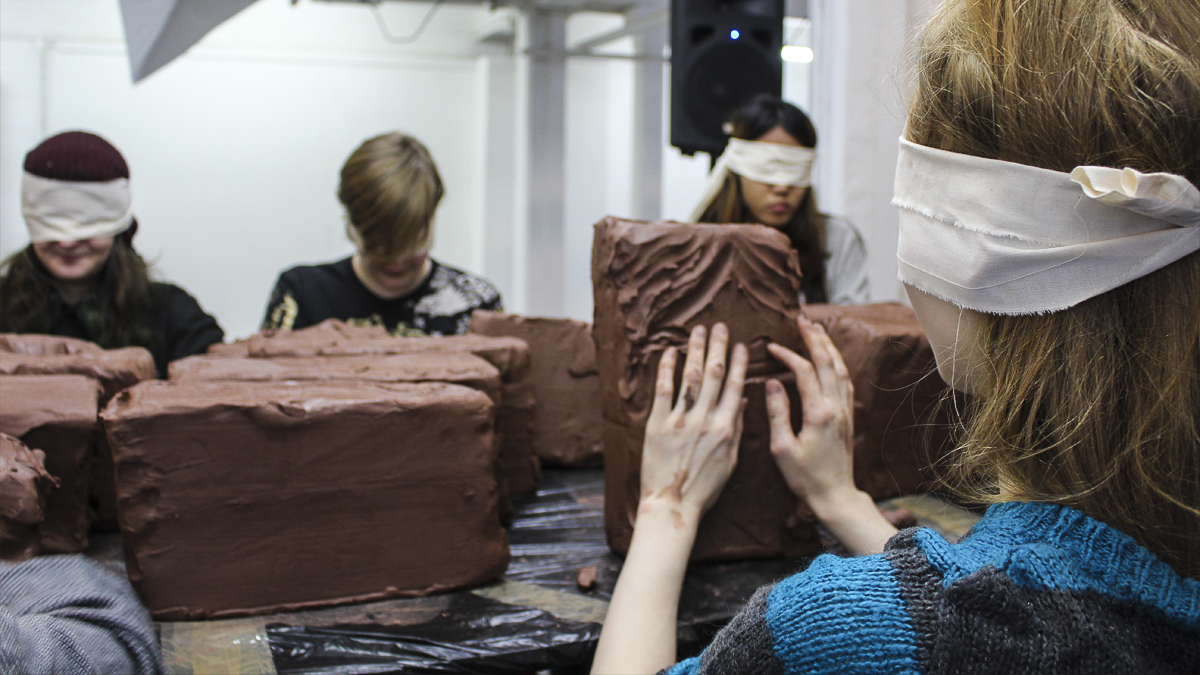 Students attending a blindfolded clay workshop