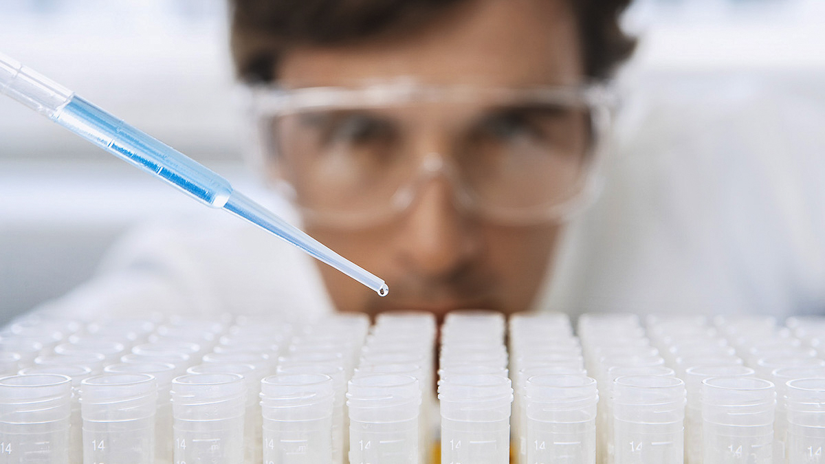 Scientist dropping chemical from pipette into test tubes
