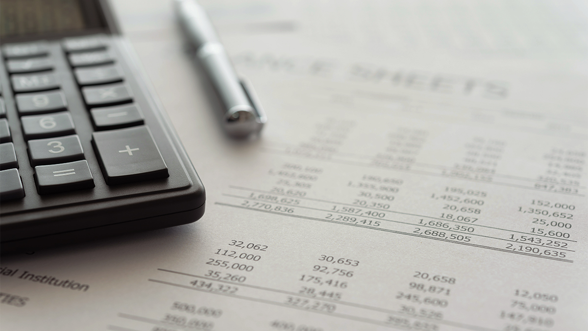 Close up of calculator, pen and a piece of paper with financial information