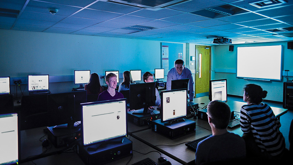 An academic helping students in a practical session in a computer lab