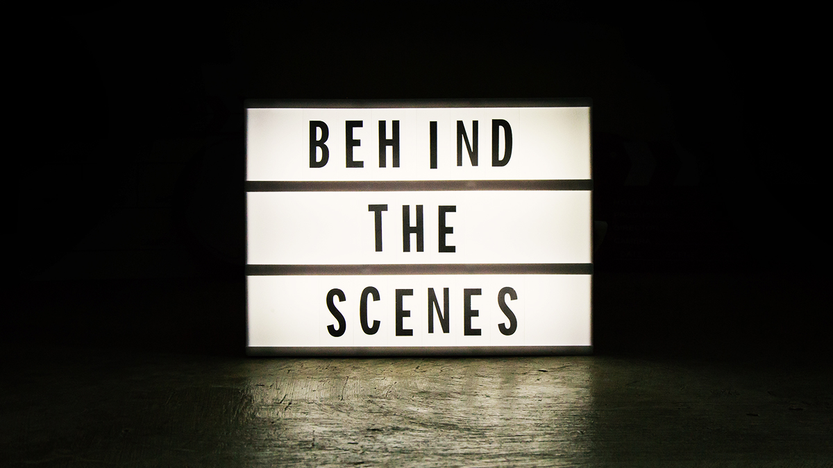 Lightbox sign that says 'behind the scenes' in a dark room