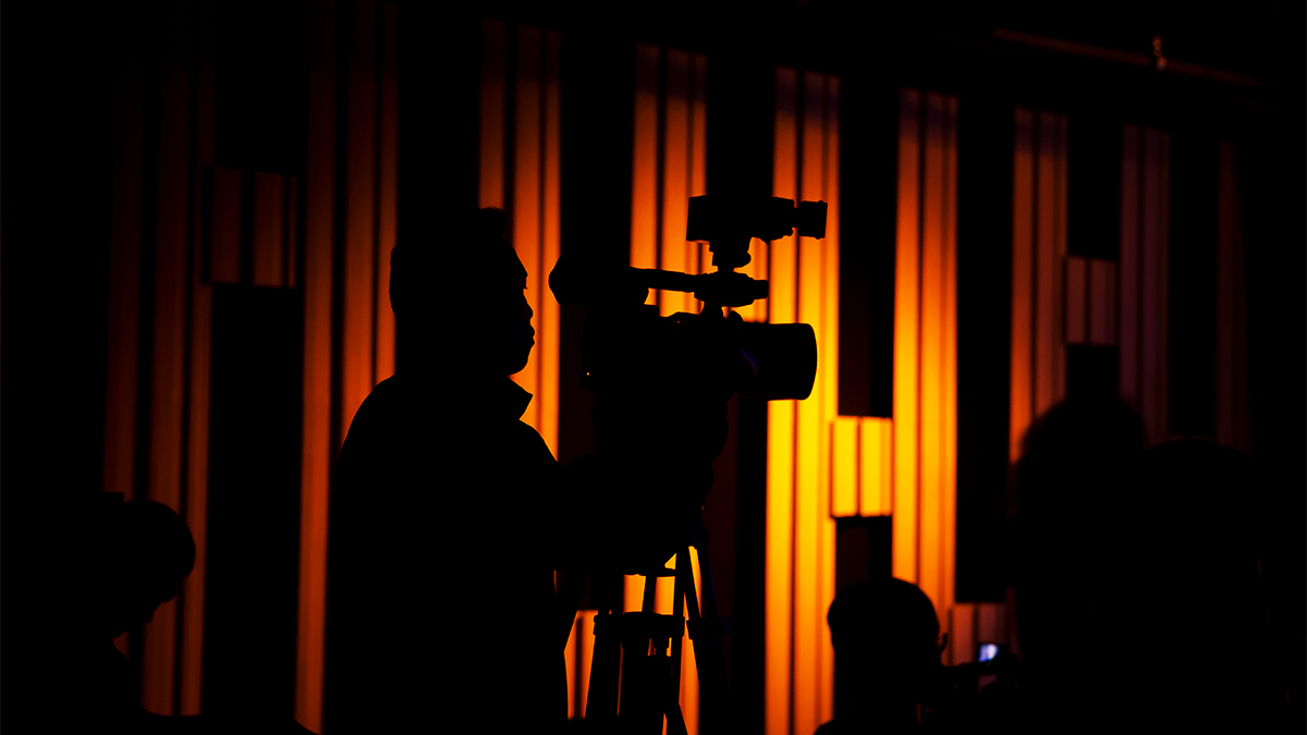 Student cameraman working in shadow in a theatre