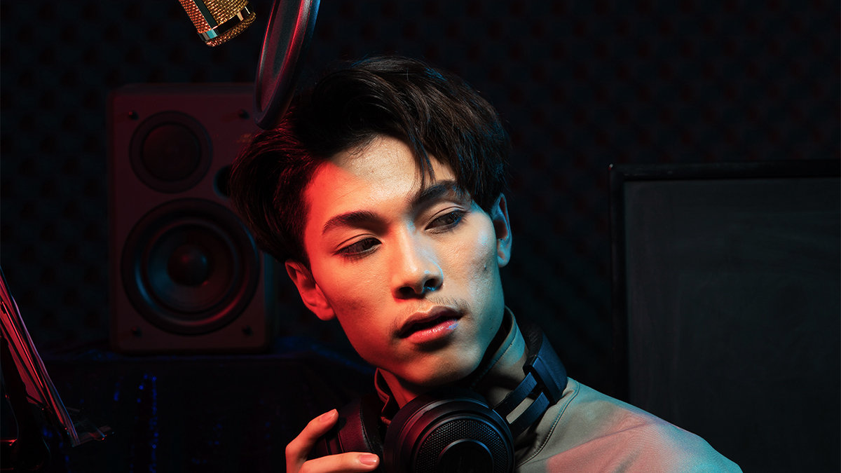 Male student with headphones round his neck, standing in a recording studio