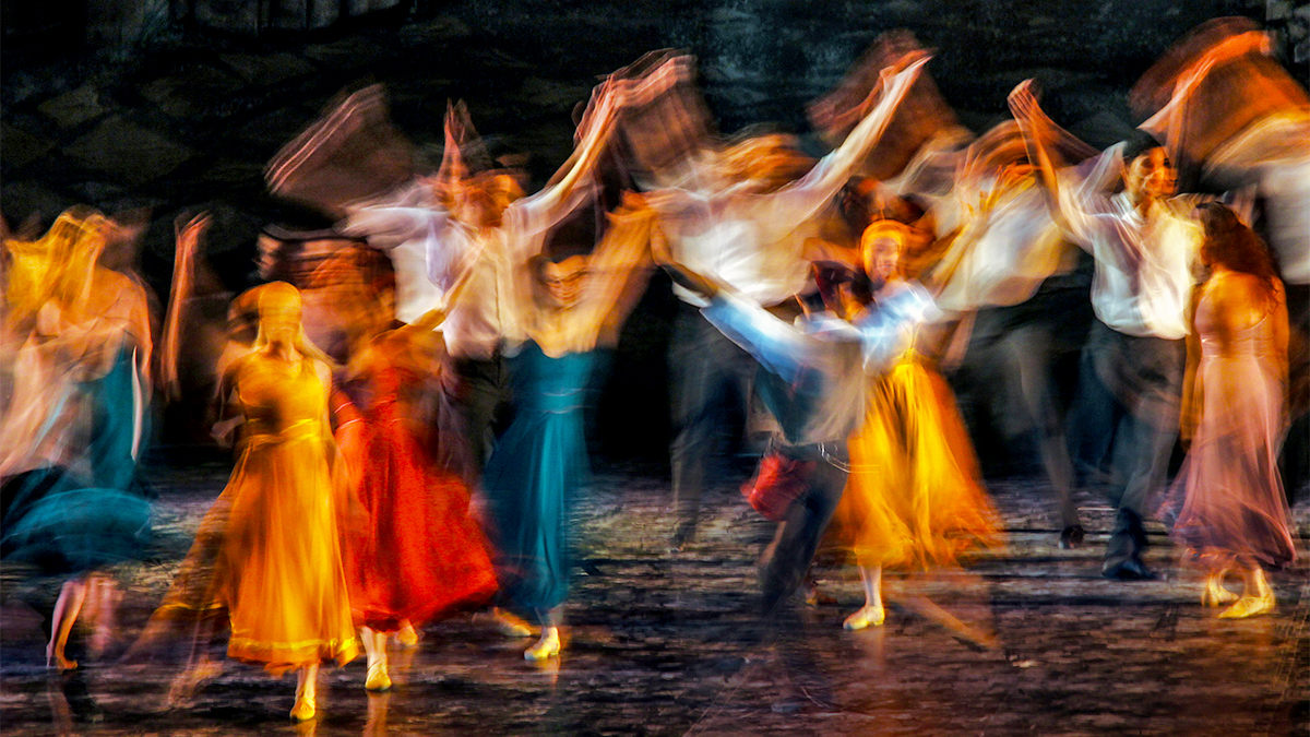 A blurred image of dancers performing on a theatre stage