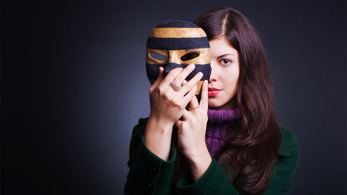A female student actor with brown hair holding a theatrical mask up partially in front of her face