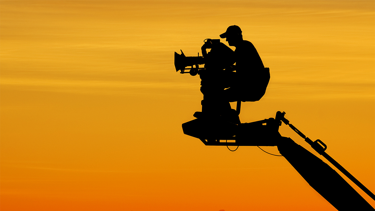 Silhouette of a film cameraman on a rig with an orange sky in the background