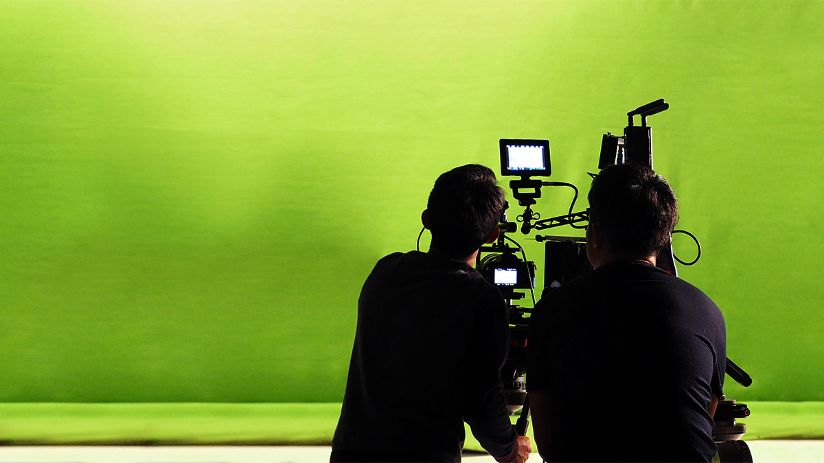 Two film students shooting a green screen