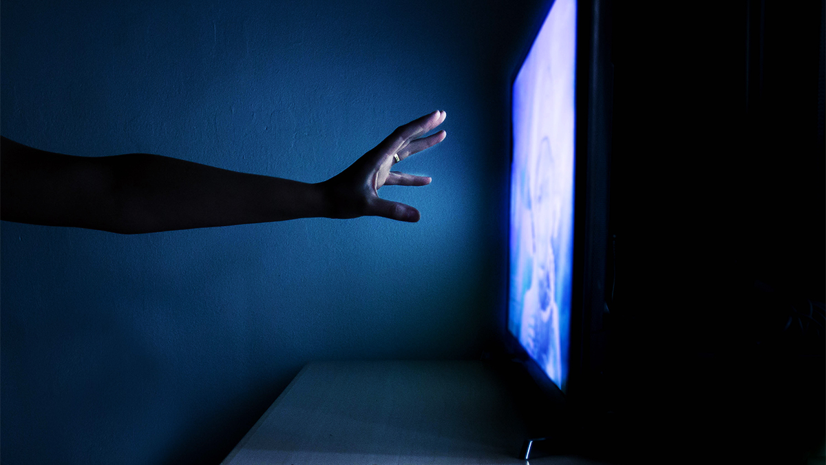Hand reaching towards television that is switched on