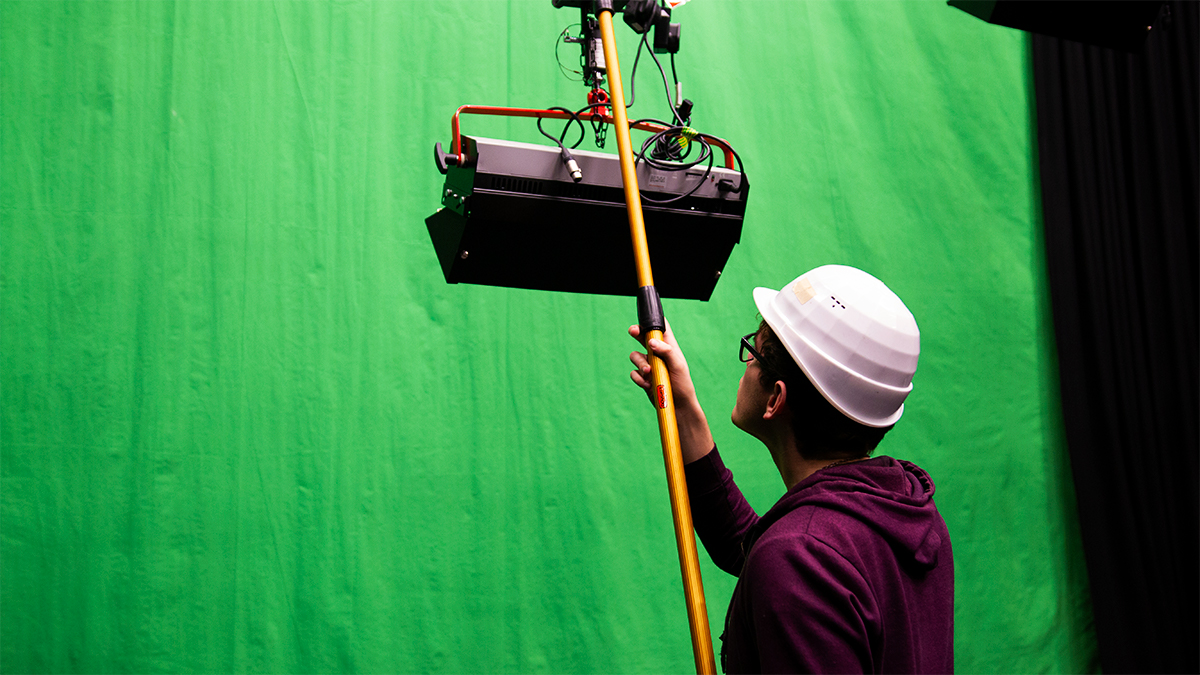 Film student adjusting lighting rig in front of a green screen in Minghella Studios