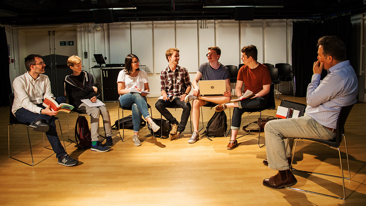 A group of students and lecturers sat around in a studio in a group discussion