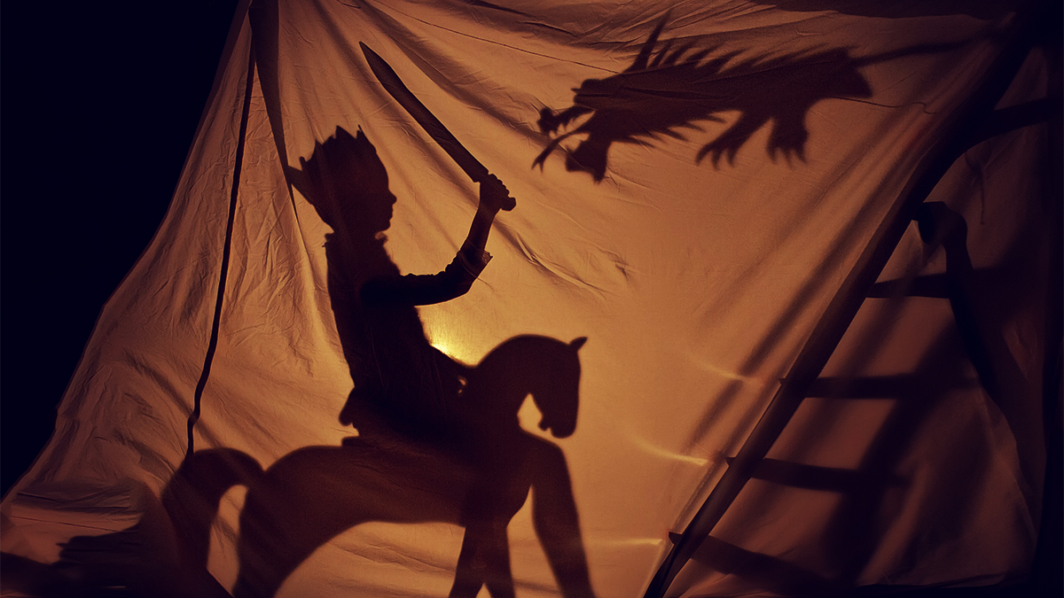 Shadowplay images against a white sheet of a knight on a horse battling a dragon