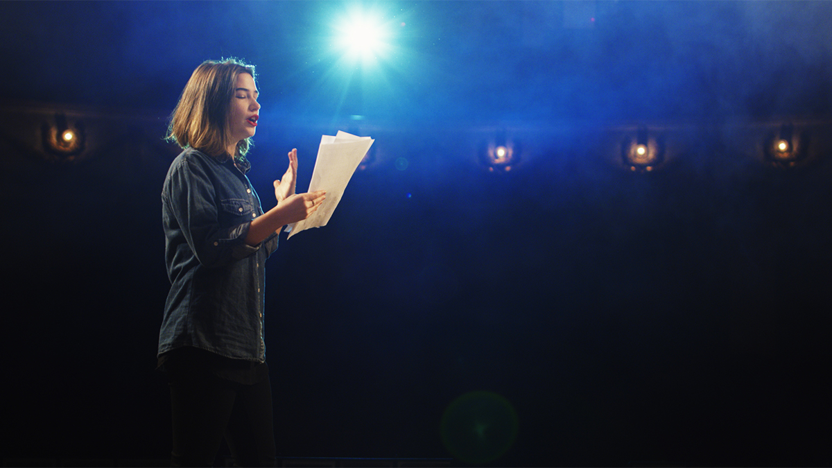 A student on stage facing the audience reading from a script