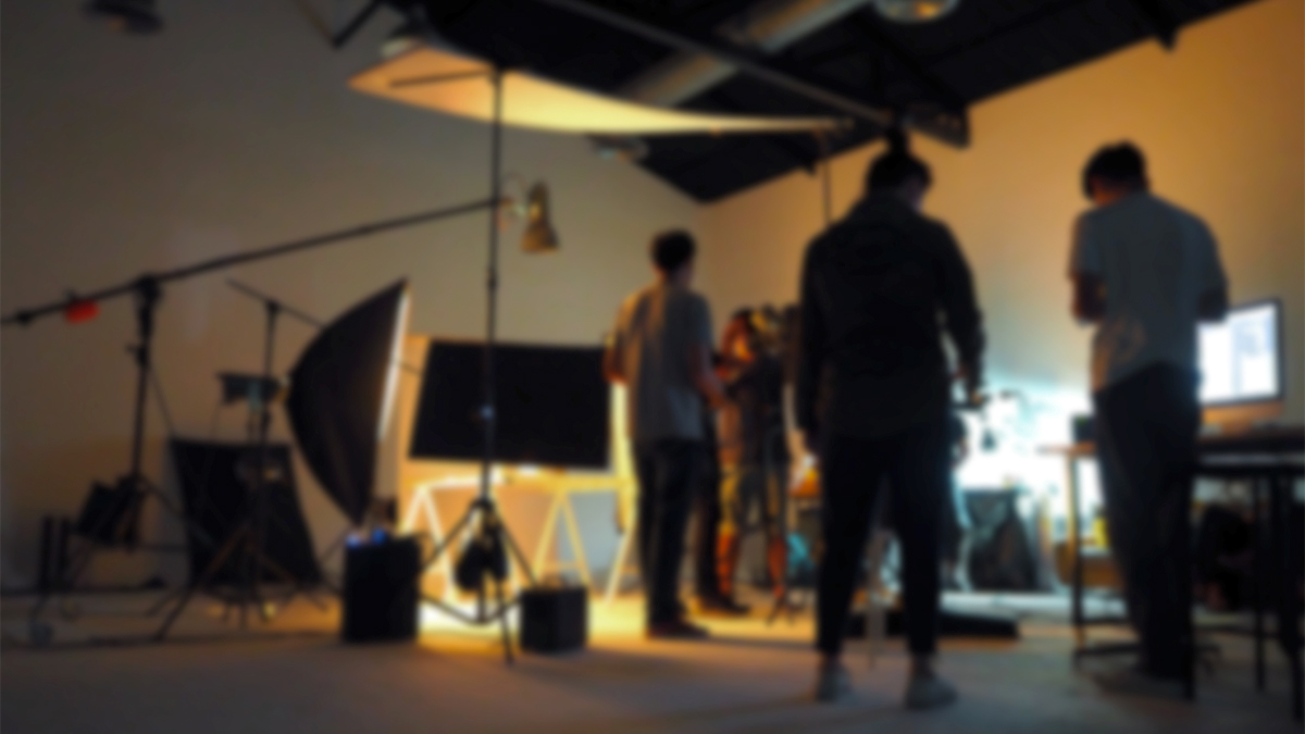 Students setting up the lighting for their film shoot in a studio space.