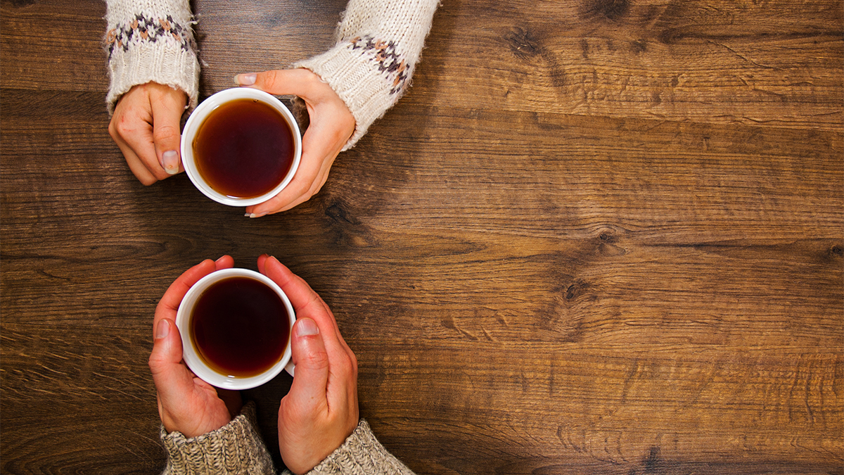 Aerial shot of two people sat at a wooden table with cups of tea