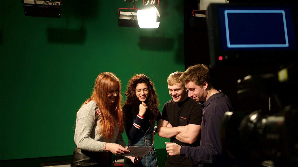 Four undergraduate students in a TV greenscreen studio looking over notes