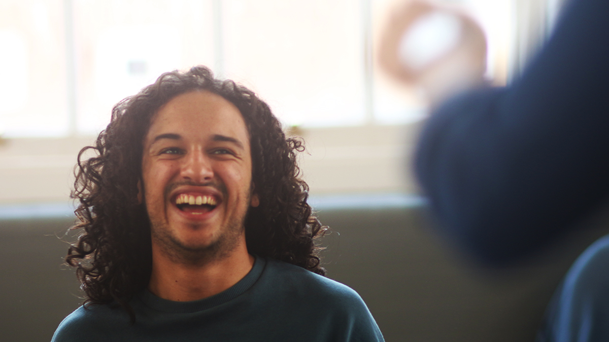 A cheerful theatre student laughing during a workshop