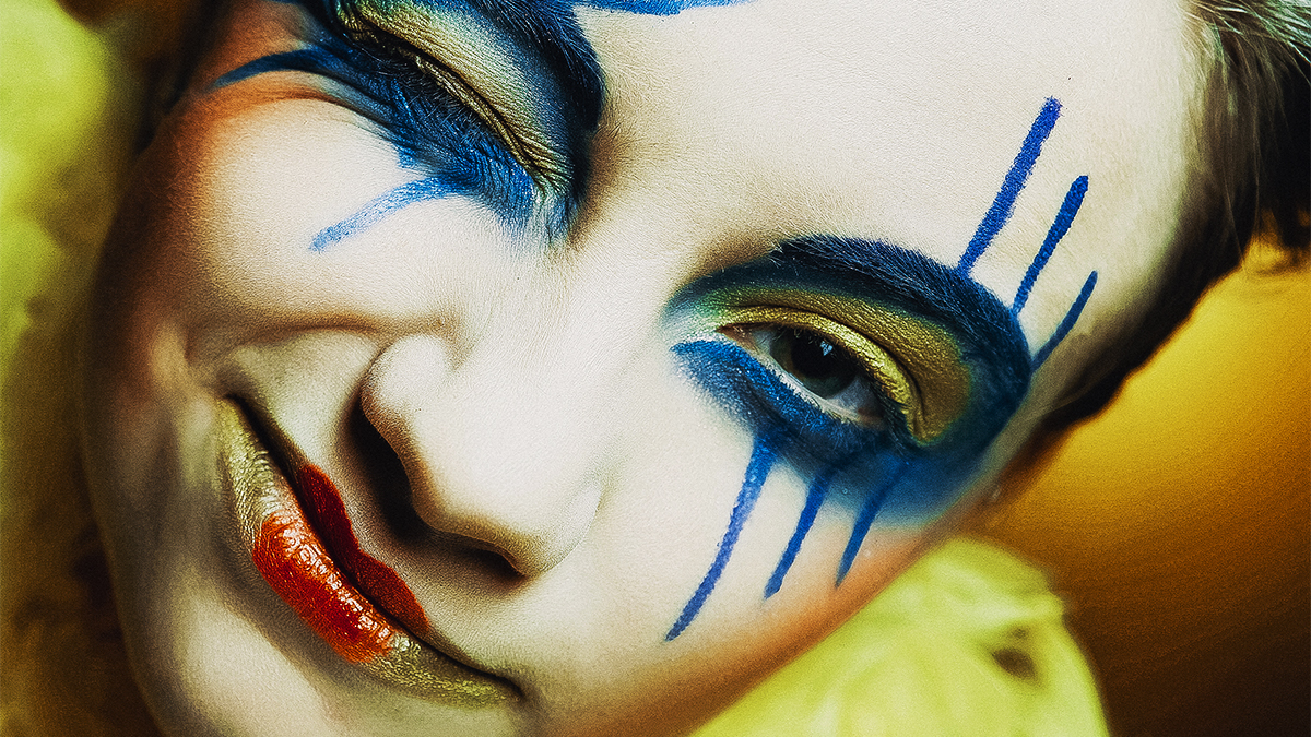 Close up of student actor winking and wearing blue and yellow make-up around their eyes