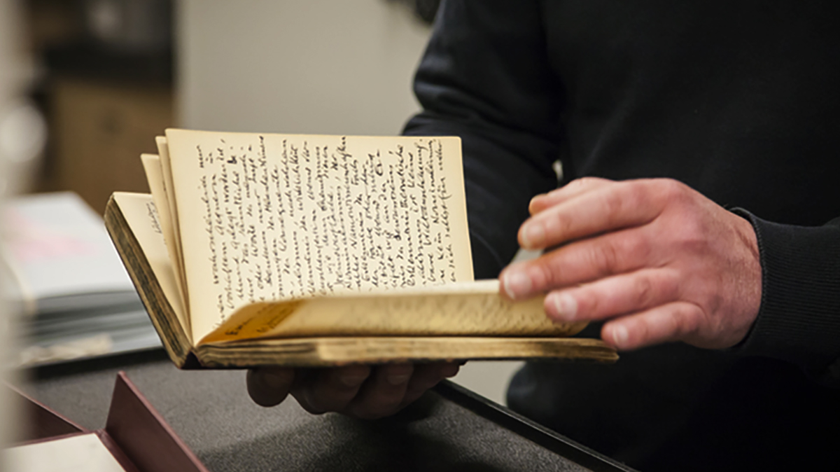 Closeup of lecturer holding a diary owned by Samuel Beckett