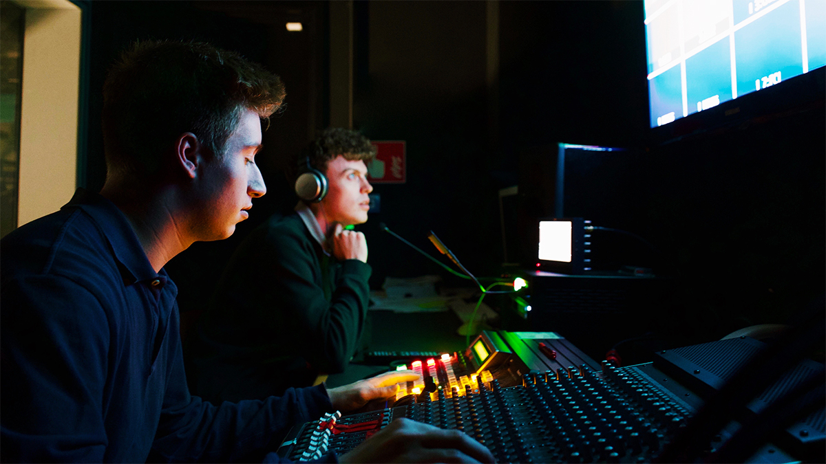 Two students sitting in a dark room with a mixing board and screens