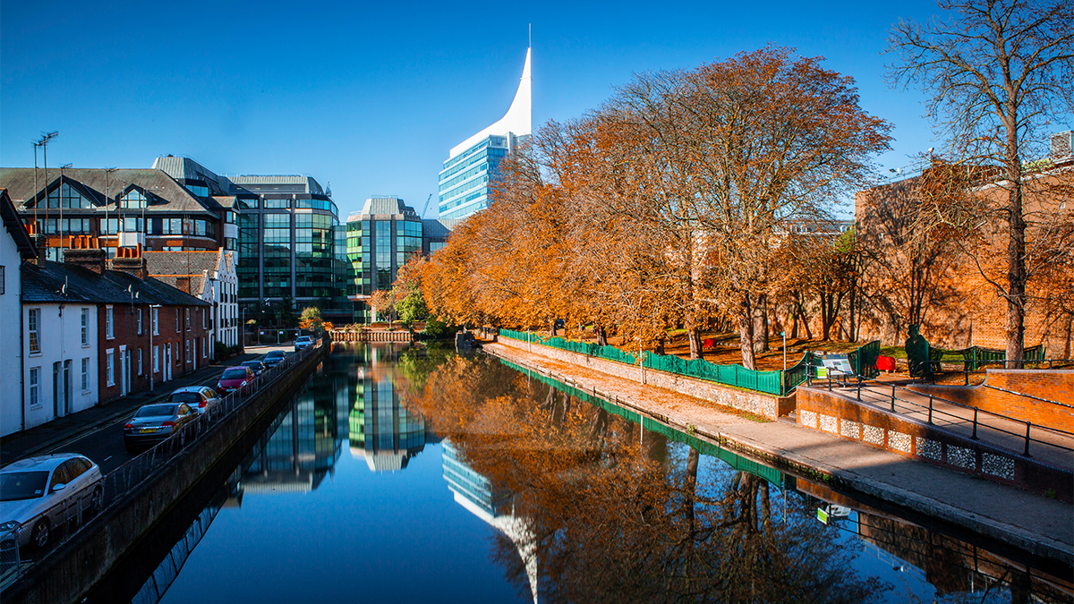 View of the Kennet canal in Reading town centre with autumnal trees and rows of houses on either side