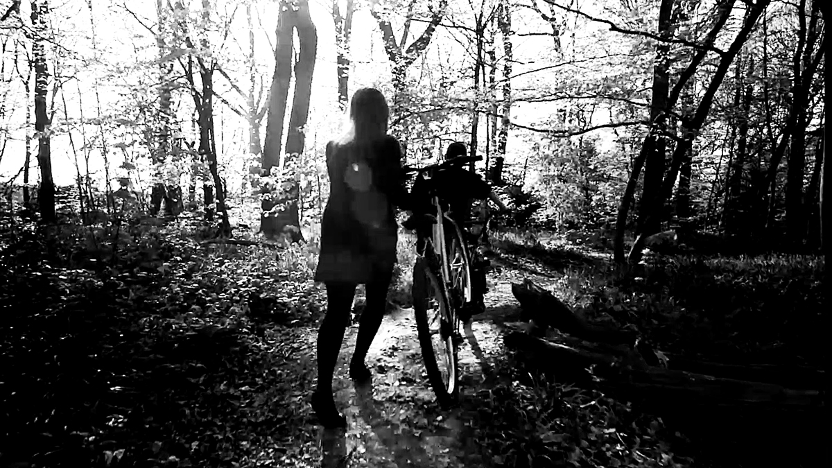 Screenshot of a student film of two people running through the woods in black and white