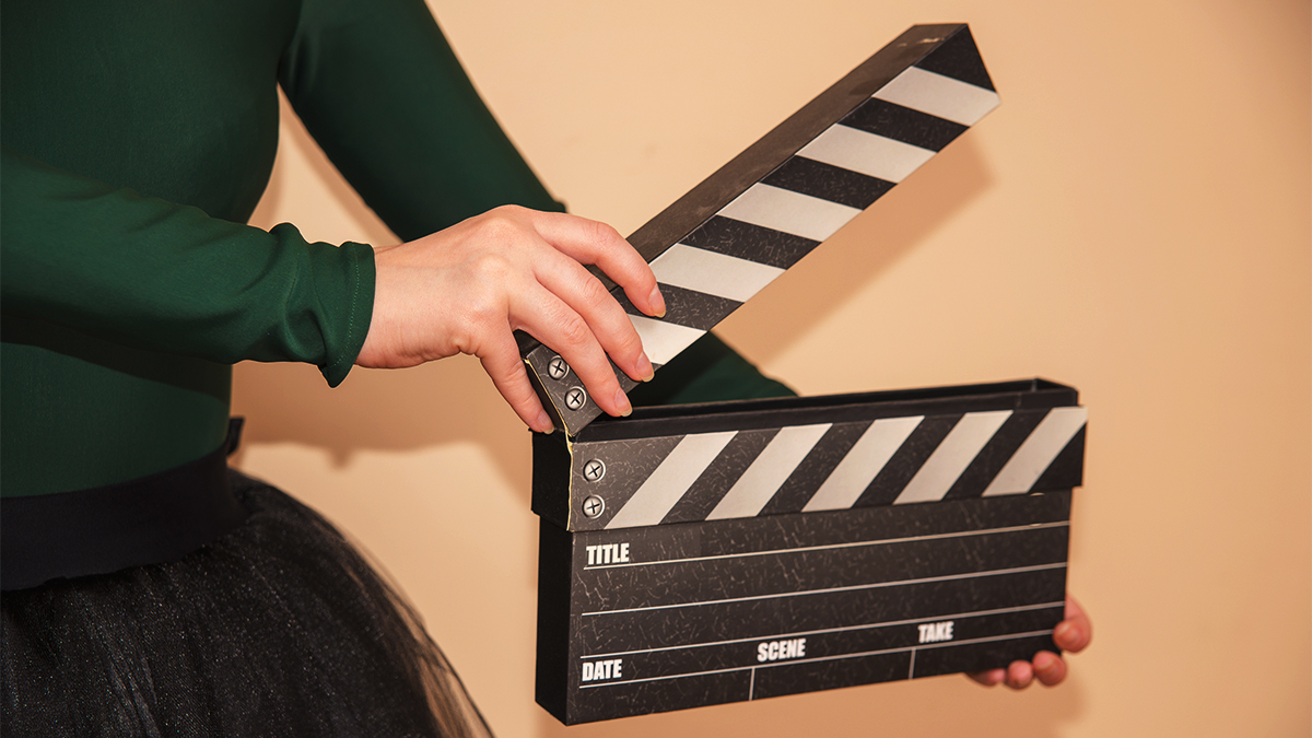 Student in a green top and black skirt holding a film clapperboard, about to close it.