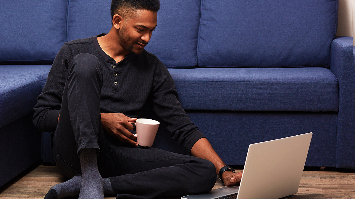 A film and theatre student sitting on the floor in front of a blue sofa, using laptop and drinking from a mug.