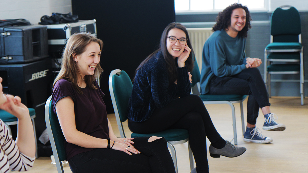 Three students sat next to eachother in chairs laughing during a workshop