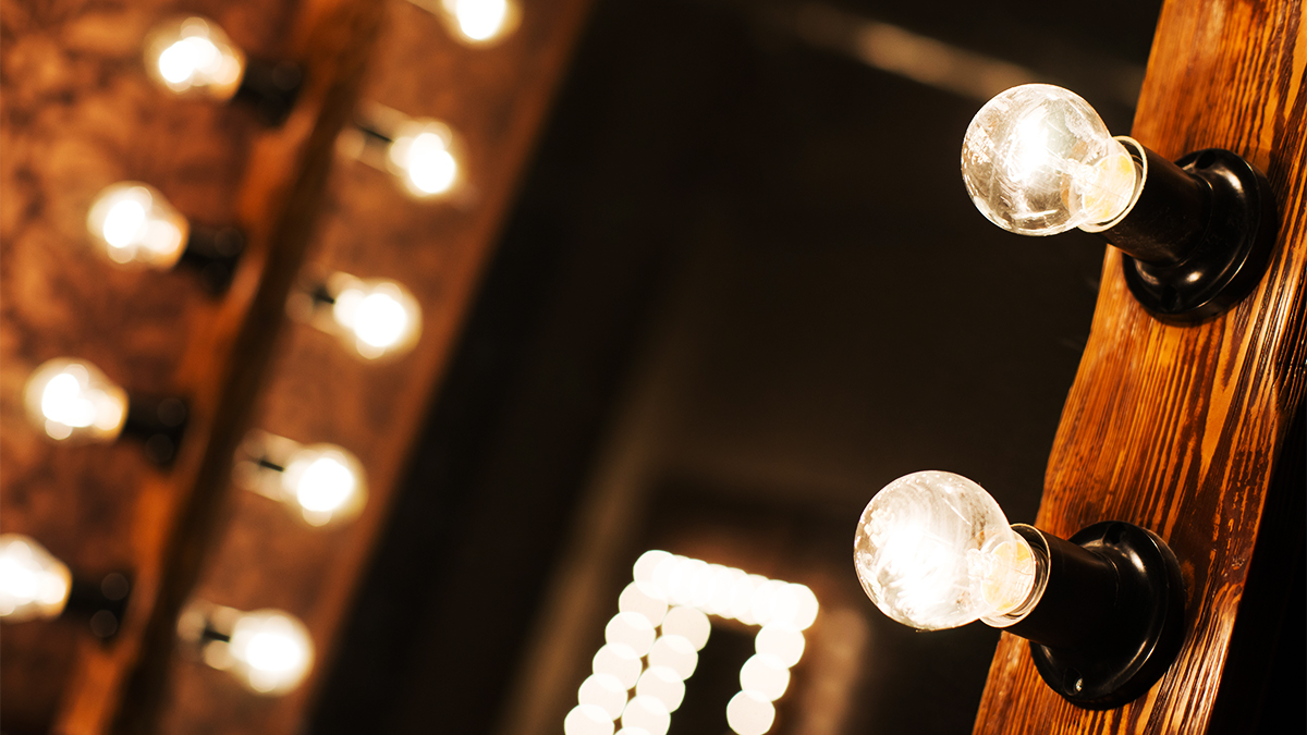 Close up of lightbulbs on a mirror in a theatre dressing room.