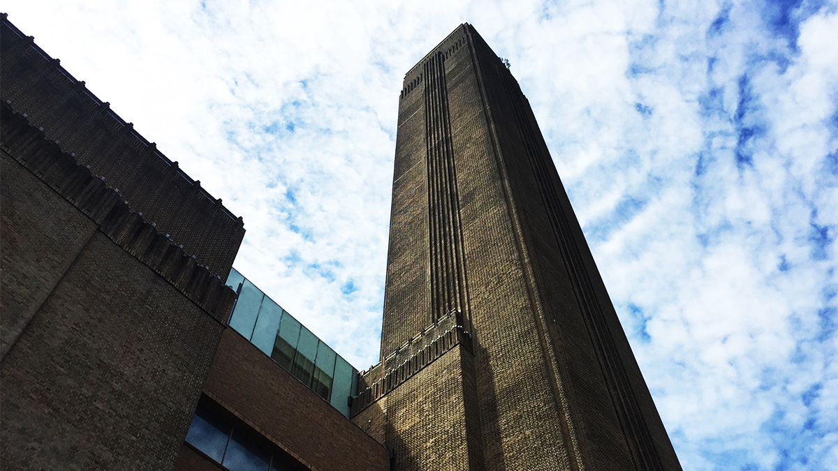 Upward facing angle of the Tate Modern smokestack against a cloudy sky