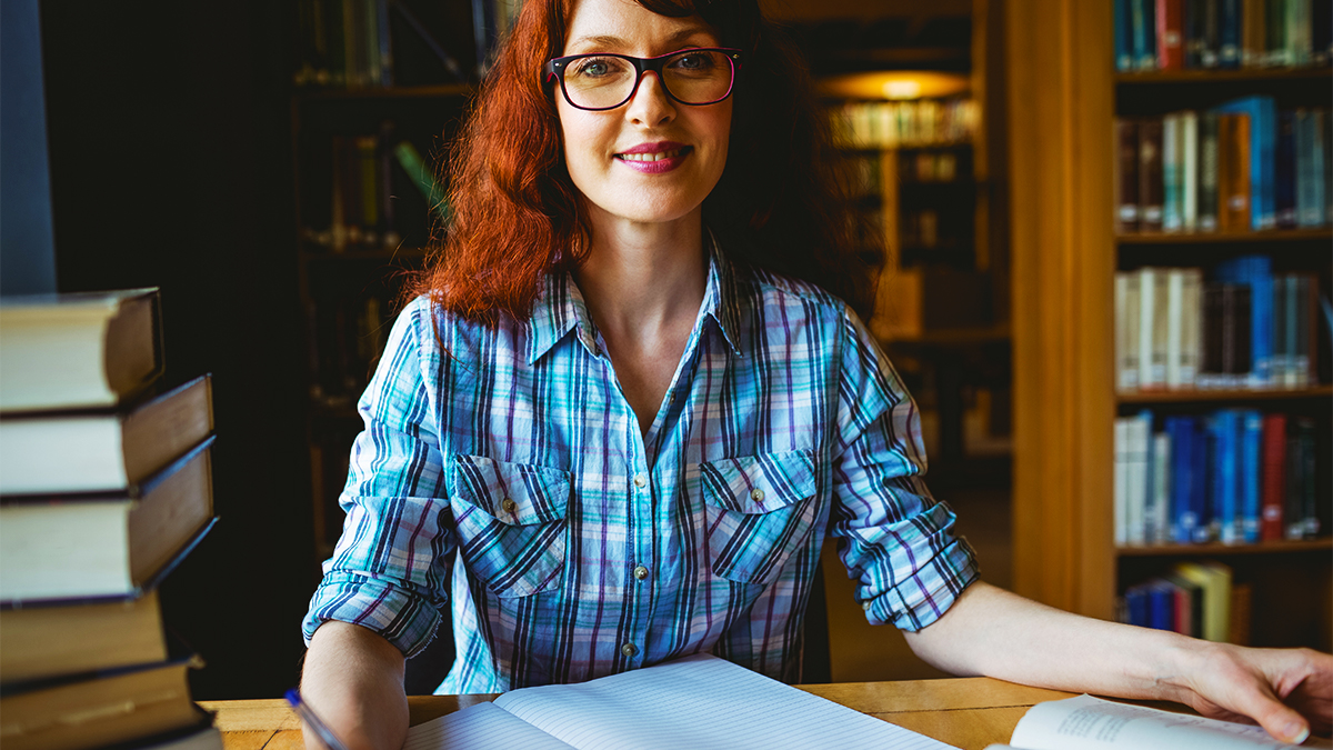 Smiling female student sitting in a library with a notebook and a stack of books