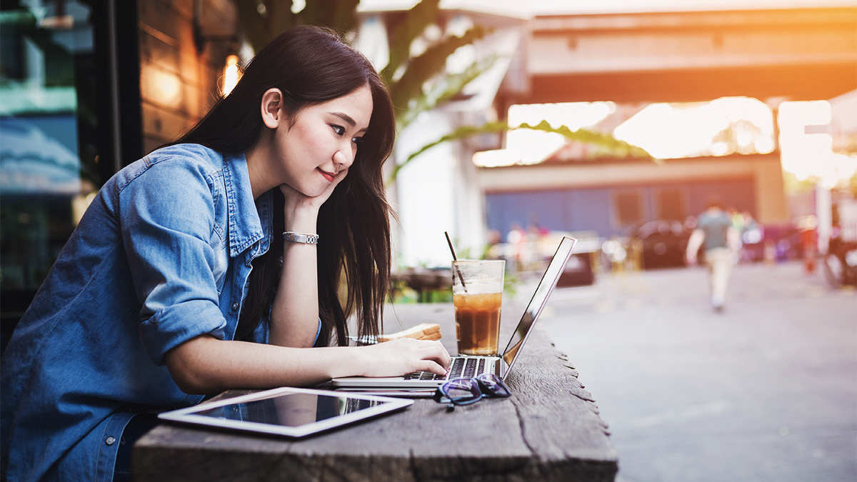 Student sitting outside of a cafe with a laptop and a cup of coffee