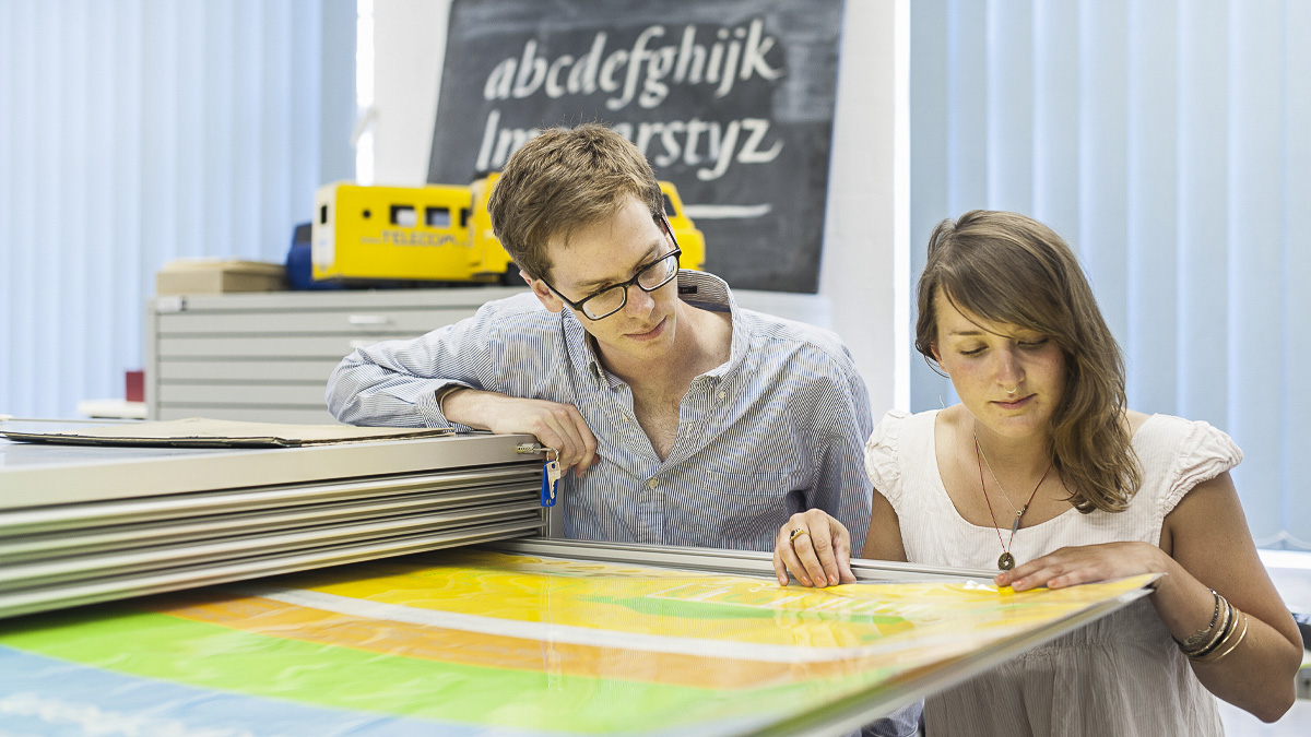 Undergraduate student and academic examine design large poster