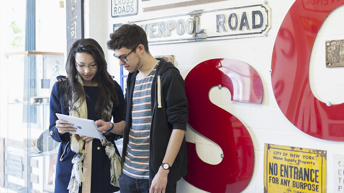 Two undergraduate students looking at a tablet standing in the Department of Typography