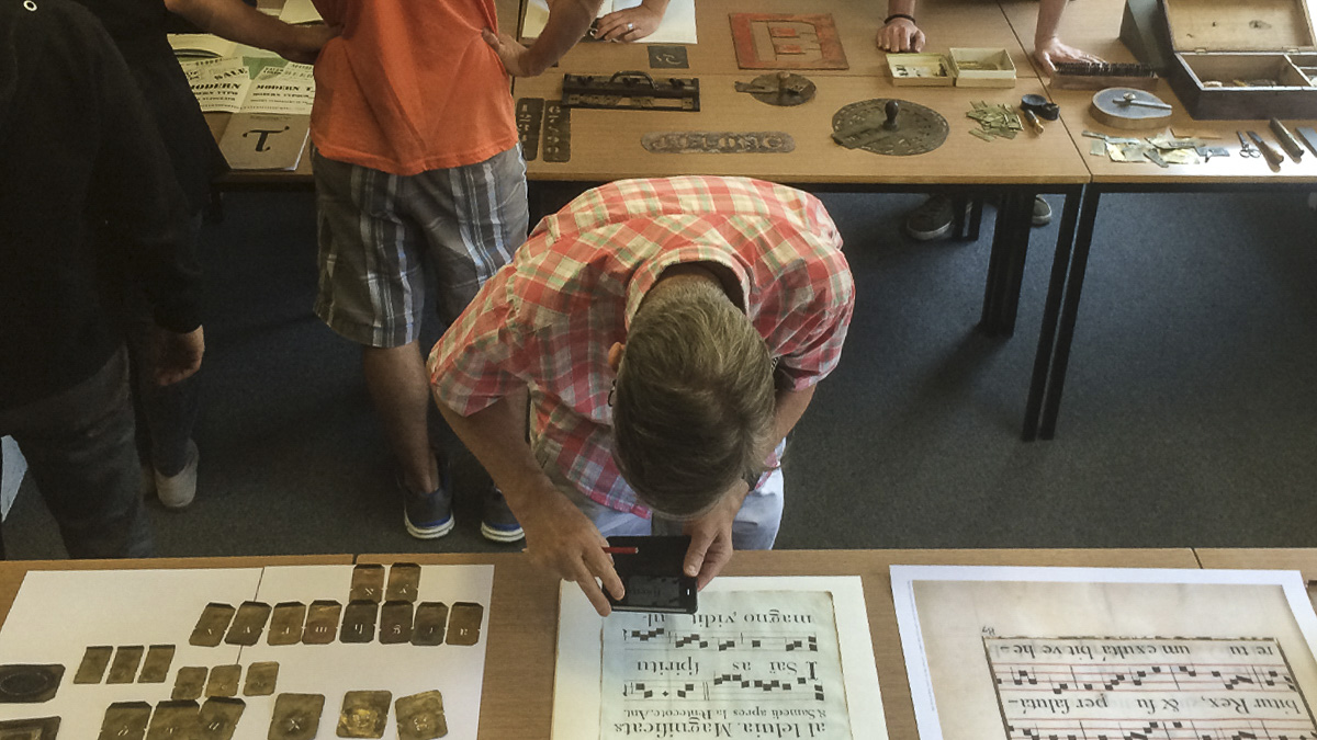 Typography student using magnifying glass to examine historic document from Department collections