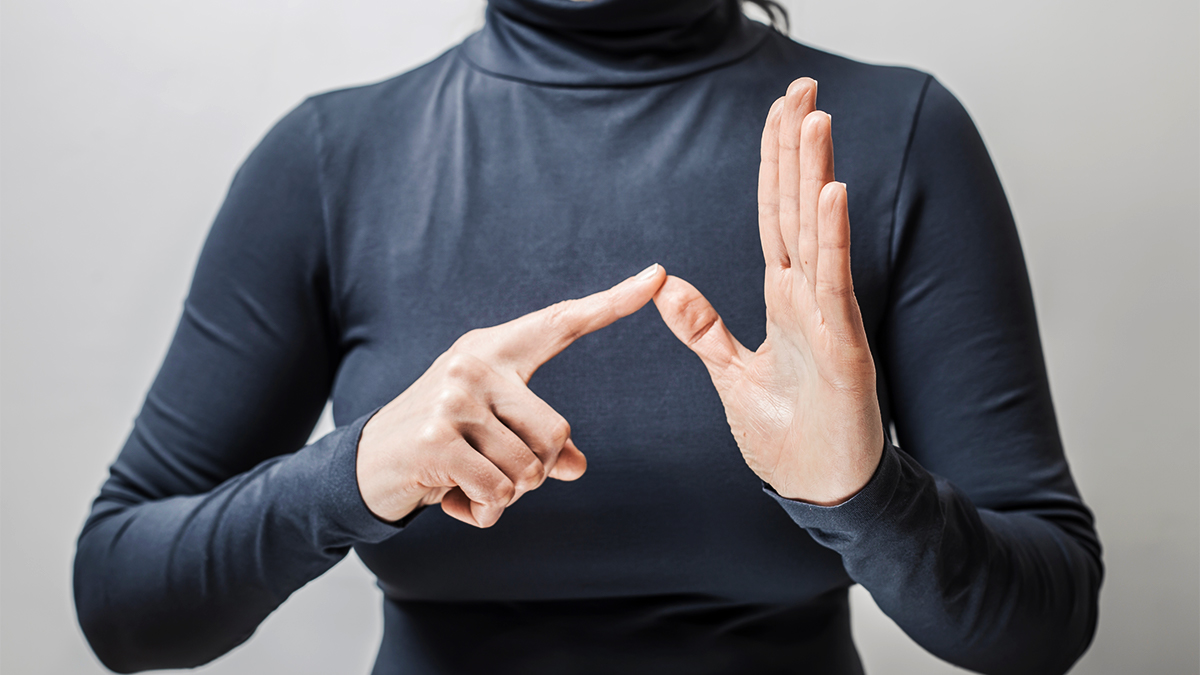 Close up of woman's hands spelling out a word in sign language