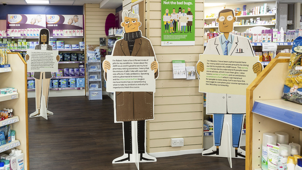Life-size cut outs of illustrated characters holding information on drug-resistant infection in a pharmacy setting