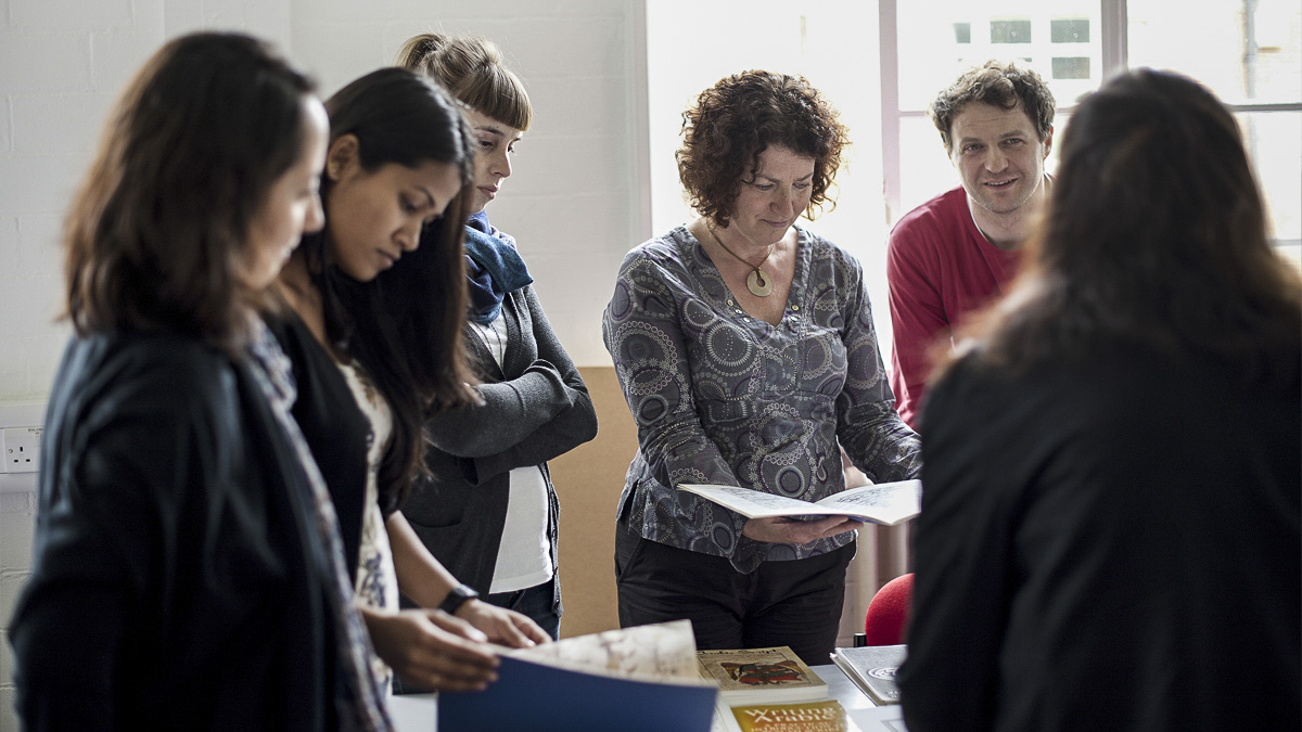 Typography professor teaching group of five master's students with books