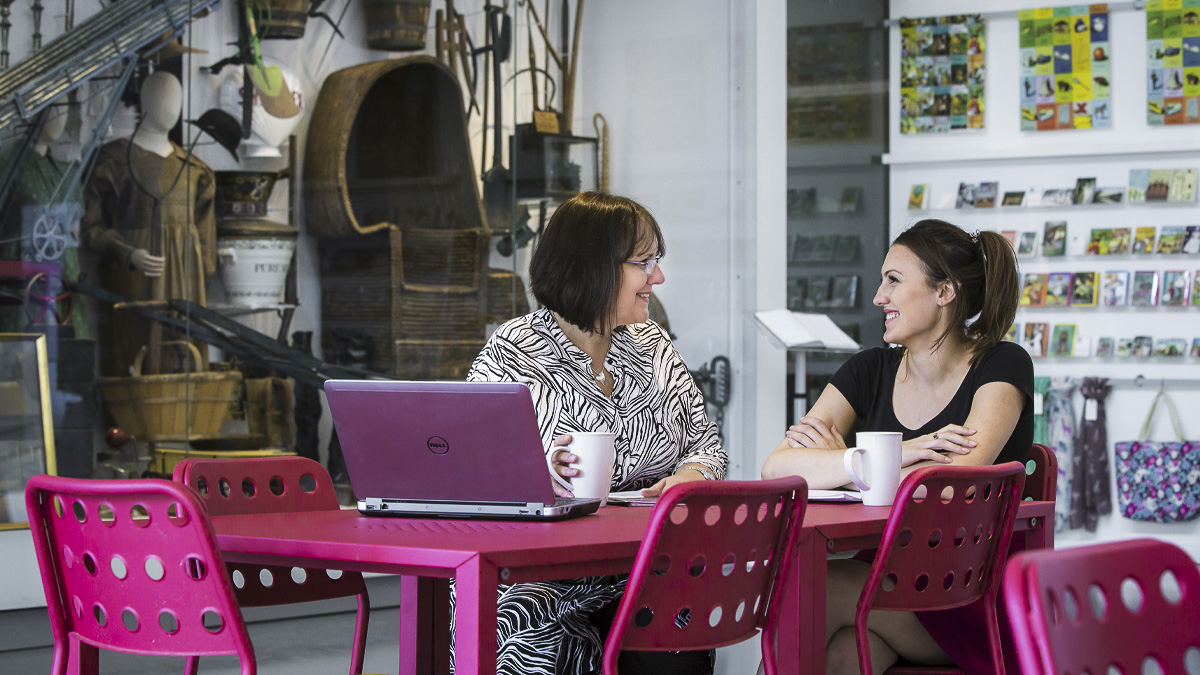 Academic and PhD student discuss thesis in a tutorial at cafe