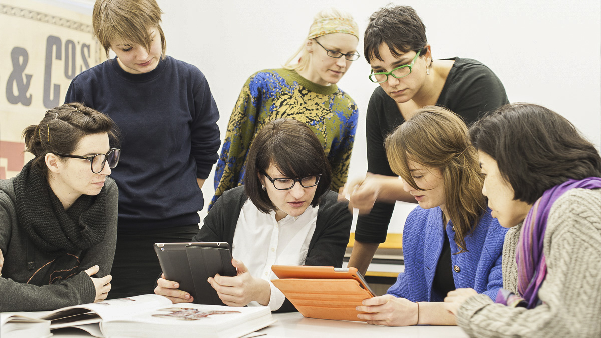 Group of students discussing design work on tablets