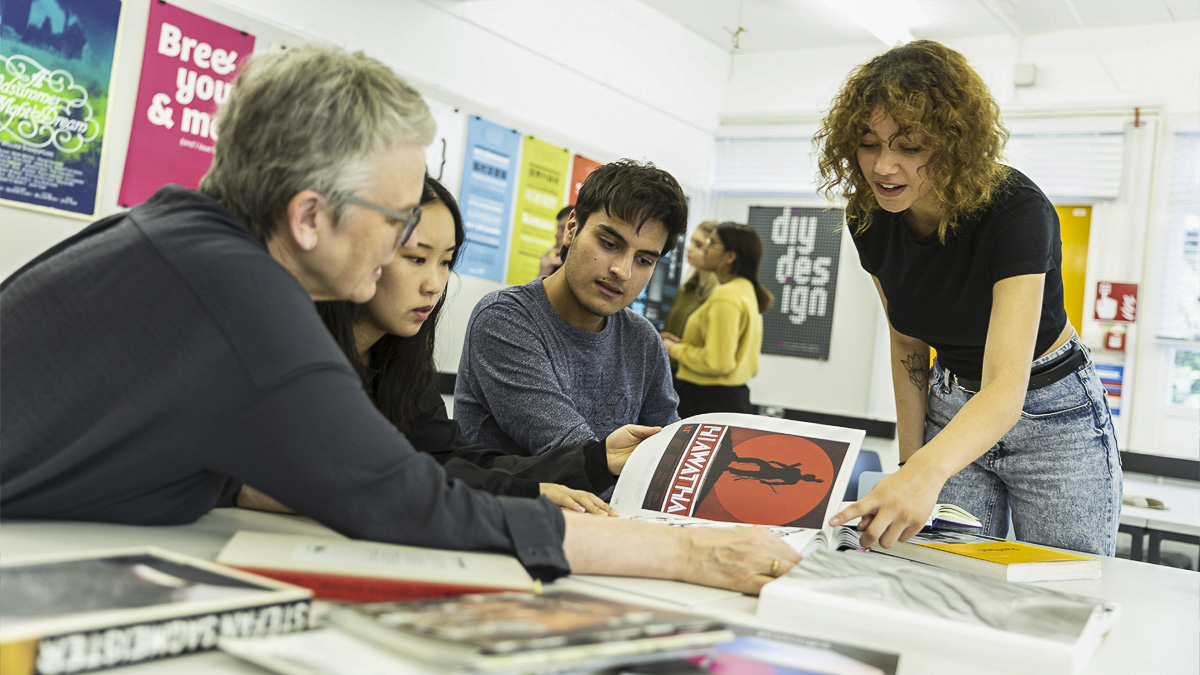 Professor Sue Walker showing examples of poster design to BA Graphic Communication students