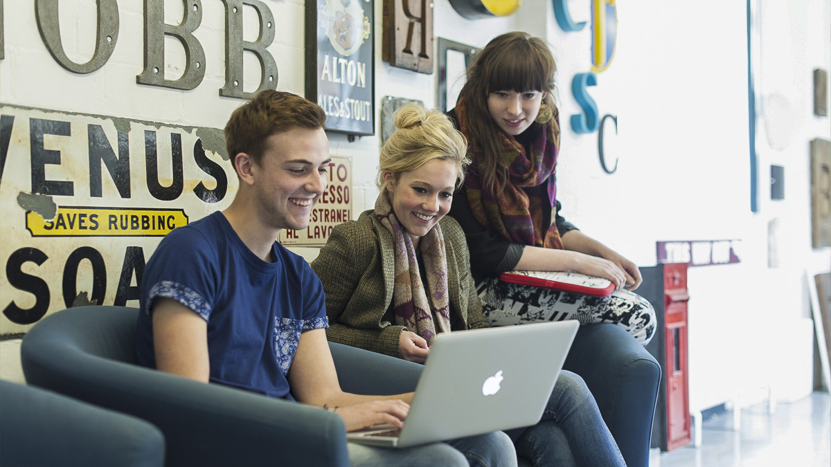 Three undergraduate students sitting on comfy chairs in Department, looking at one student's laptop