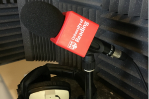 A microphone in a radio booth with a University of Reading logo