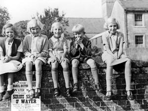 Archive photograph of children sitting on a wall